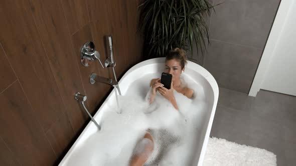 Įprotis maudytis vonioje su telefonu